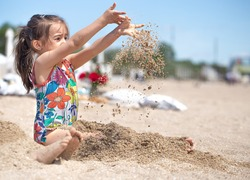 Little girl playing with sand on the beach. A cheerful child. The concept of summer vacation.