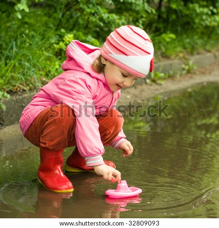little girl playing with ship in the puddle