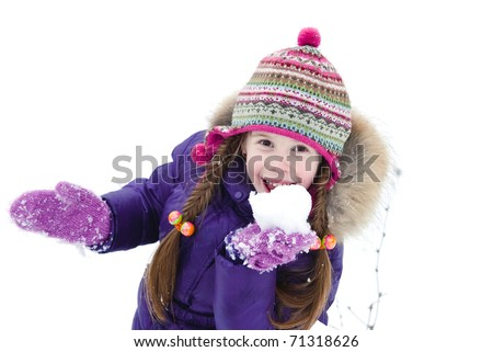 little girl playing with snow in a winter woods