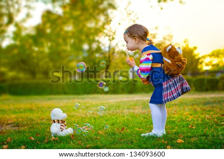 Little girl playing with soap bubbles and Teddy bear in park.