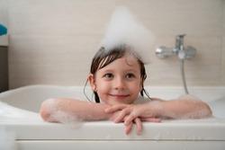 little girl playing with soap foam in bath