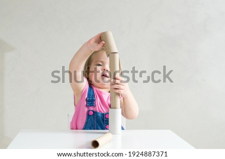 Little girl playing with toilet paper rolls and cardboard tube. Games and toys made paper tube for babies and toddler, activities Montessori in our home, child development and occupational therapy Stock foto ©