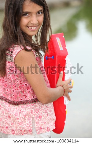 Little girl playing with toy boat