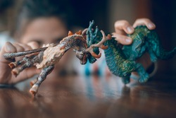 Little girl  playing with toys.Fantastic character children toys characters, dragons.Closeup.