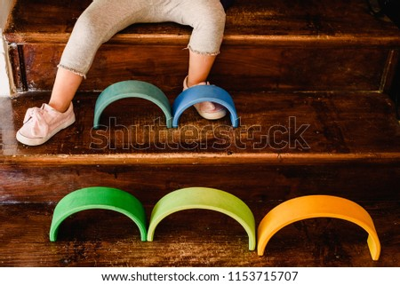 Little girl playing with waldorf montessori rainbow of various colors