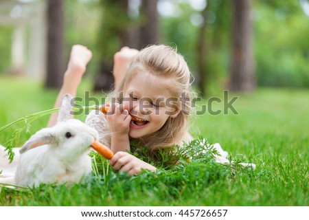 Stock Photo Little girl playing with white rabbit in summer day outdoor