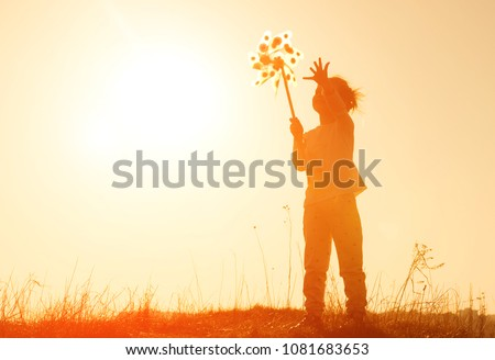 Little girl playing with wind toy or pinwheel against the sky at sunset. Happy girl silhouette