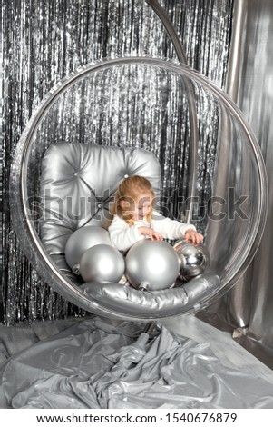 Little girl plays in a chair a glass bowl with silver balls. Snow queen cover.