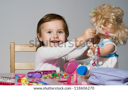 Little girl plays with a doll