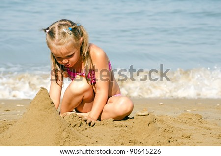 Little girl plays with sand sea coast