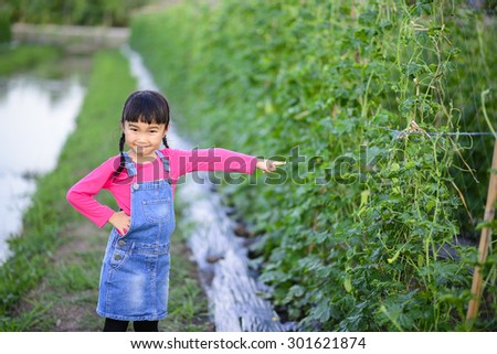 Little girl point to the product in the garden