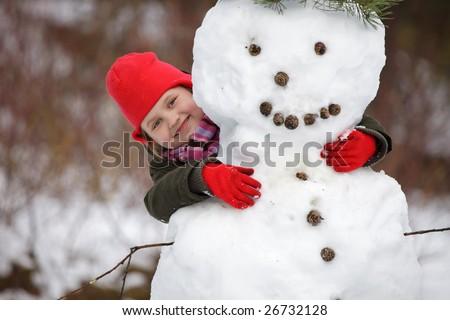 Little girl portrait, happy posing with snowman
