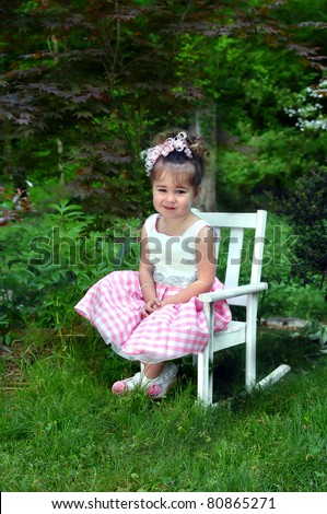 Little girl poses on a white, wooden rocking chair.  She is dressed in her Easter outfit and is smiling happily.  Spring green surrounds her outdoors. - stock photo