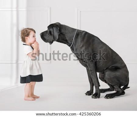 Little girl posing against a big dog