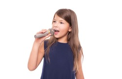 Little girl posing with a microphone for singing on a white background.