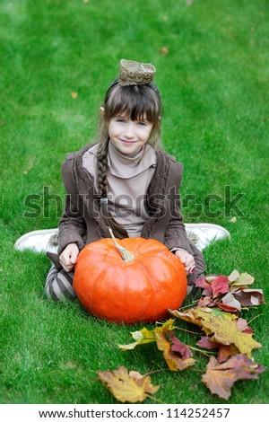 Little girl posing with big orange pumpkin on grass