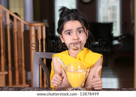 little girl posing with orange juice