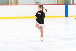 Little girl practicing figure skating on an indoor ice skating rink.