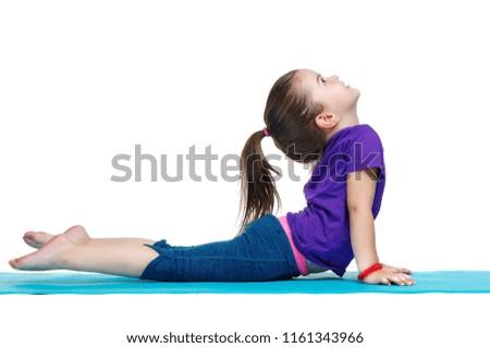 Little girl practicing upward dog yoga pose