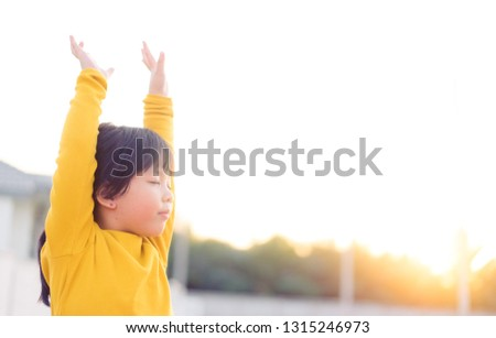 Little girl praying and raise hands in the morning for faith, spirituality and religion.  #1315246973