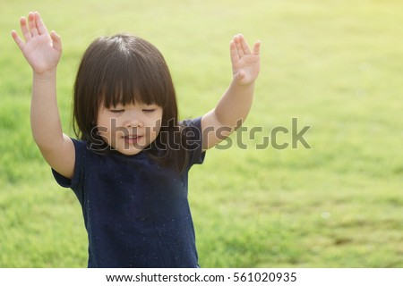 Little girl praying and raise hands in the morning for faith, spirituality and religion.