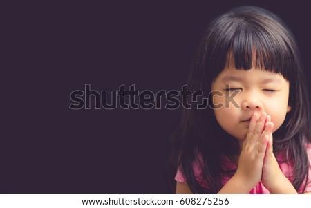 Little girl praying in the morning.Little asian girl hand praying,Hands folded in prayer concept for faith,spirituality and religion.Black  - Shutterstock ID 608275256