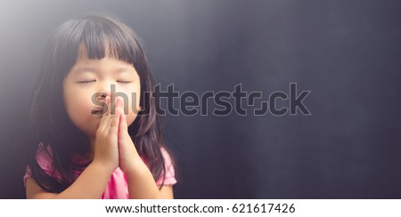 Little girl praying in the morning.Little asian girl hand praying,Hands folded in prayer concept for faith,spirituality and religion.Black background.
