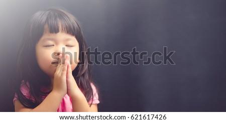 Little girl praying in the morning.Little asian girl hand praying,Hands folded in prayer concept for faith,spirituality and religion.Black background. #621617426