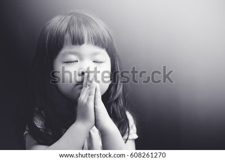 Little girl praying in the night.Little asian girl hand praying,Hands folded in prayer concept for faith,spirituality and religion.Black and white tone.