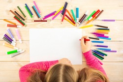 Little girl prepares to paint on a blank sheet of paper. Drawing is done by a child with colored pencils or felt-tip pens. Children's drawing. View from above.