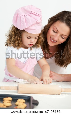 Little girl preparing a daughter with her mother in the kitchen