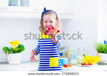 Little girl preparing breakfast in kitchen. Healthy food for children. Child drinking milk and eating fruit. Happy preschooler kid enjoying morning meal, cereal, banana and raspberry. Kids cooking.