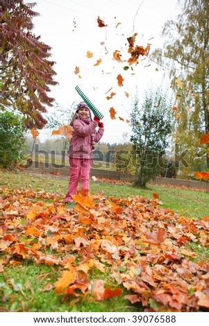 Little girl rake colorful fallen autumn leaves in garden and having fun