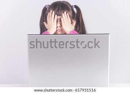 Little girl reacts while using a laptop. Internet safety and parental control concept