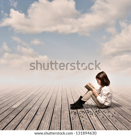 little girl reading a book on a wharf