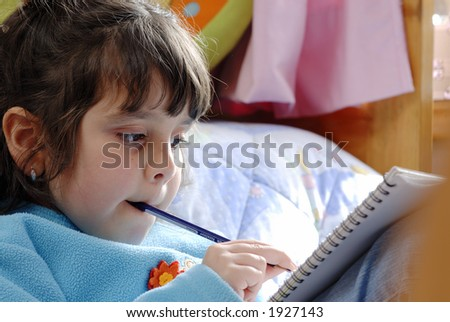little  girl reading  and biting a pencil over a bed