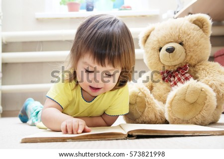little girl reading book lying on stomach in her room on carpet with toy Teddy bear, smiling cute child, children education and development, happy childhood #573821998