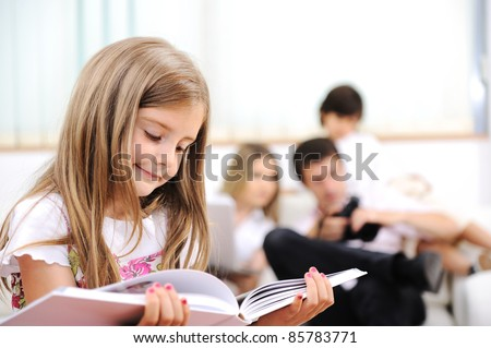 Little girl reading in home, indoor with happy family