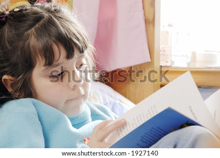 little girl reading over a bed - stock photo