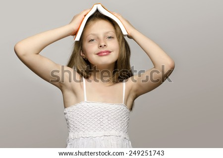 Little girl reading some books, kid learning, child studying, child having fun with a book.\ Girl with a book on her head smiling and thinking, preparing for school