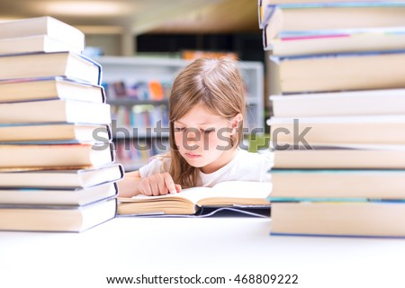 Little girl reads a book surrounded with piles of books in library. Education and Back to school concept.  #468809222