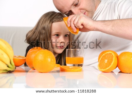 Little girl really fascinated with orange juice making. Studio shot on white background and sofa.