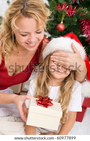 Little girl receiving surprise christmas present from her mother