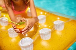 Little girl relaxing in swimming pool, enjoying suntans, drink a juice on inflatable yellow mattress in water on family vacation, tropical holiday resort