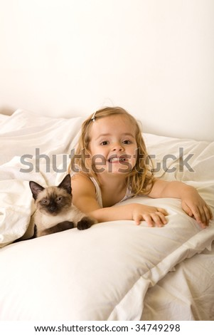 Little girl relaxing on the bed with her kitten