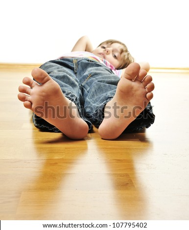 little girl resting on a wooden floor