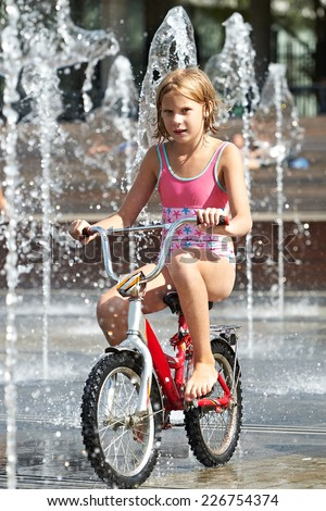 Little girl rides his bike among fountains in summer day