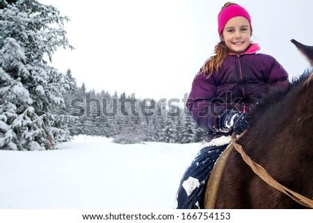 Little girl riding horse in winter