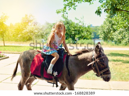 Little girl riding on a donkey