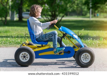 Little girl riding on pedal karting. #431599012